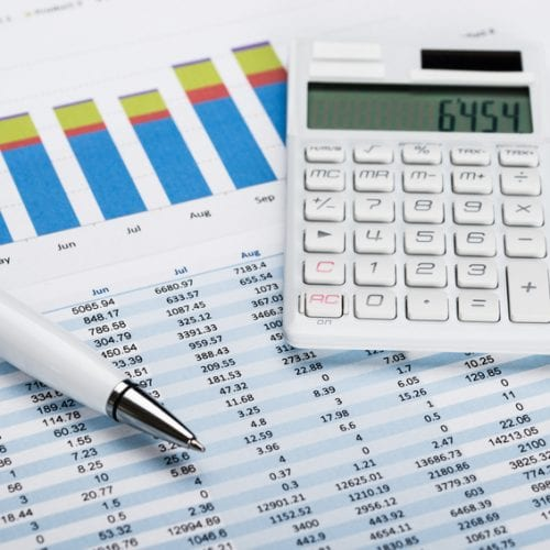 Close-up Of A Financial Data Sheet With Calculator And Ballpen